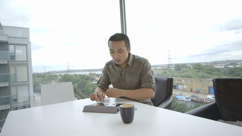 Young man sitting in office and using digital tablet Footage