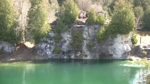 Kids are jumping from cliff into a lake (High Definition) Stock Video Footage