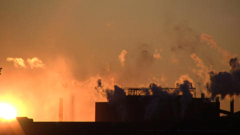 Exhaust from a factory is backlit during sunset (High Definition) Footage