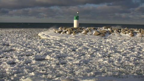 Waves crash against lighthouse amidst snow covered water... Stock Video Footage