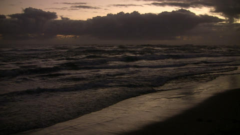 Waves gently wash up onto beach before sunrise (High... Stock Video Footage