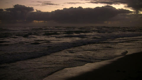 Waves gently wash up onto beach before sunrise (High Definition) Footage