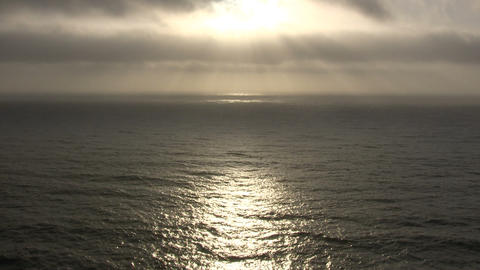 Sunlight reflects on the ocean surface as clouds pass by Footage
