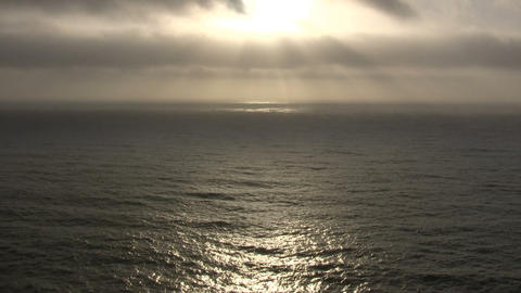 Sunlight reflects on the ocean surface as clouds pass by Stock Video Footage