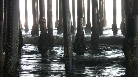 Ocean waves splash against the pier's support columns... Stock Video Footage