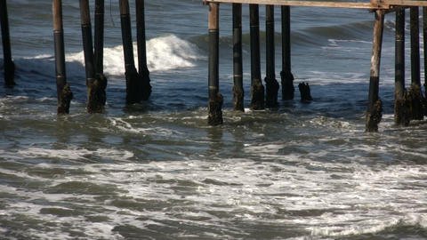 Ocean waves splash against the pier's support columns (High Definition) Footage
