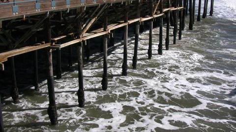 Ocean waves splash against the pier's support columns (High Definition) Footage