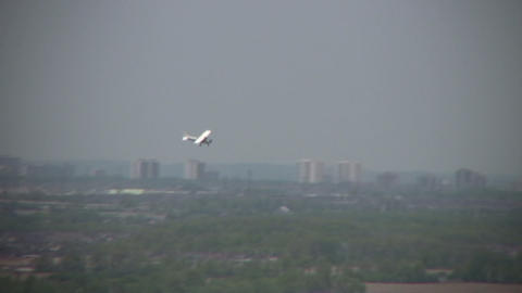 Propeller airplane flies through the air over city (High... Stock Video Footage
