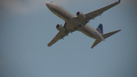 Closeup of a commercial jet ascending through the blue sky Footage