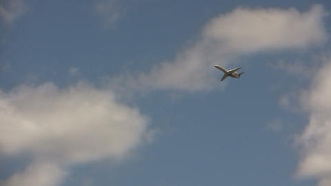 Commercial jet flies through the cloudy blue sky Stock Video Footage