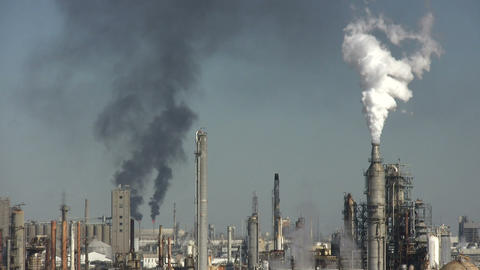 Fumes spill out of large chimneys at Houston BP Refinery Footage