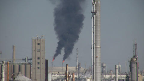 Black fumes spill out of large chimneys at Houston Refinery Stock Video Footage