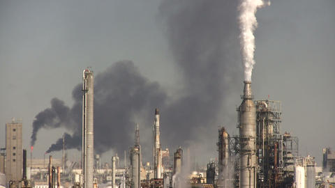 Fumes spill out of large chimneys at Houston BP Refinery Stock Video Footage