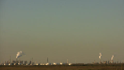 Fumes billow out of large chimneys at Houston BP Refinery Stock Video Footage