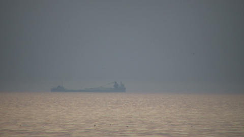 Transport ship passes by in the hazy distance (High Definition) Footage