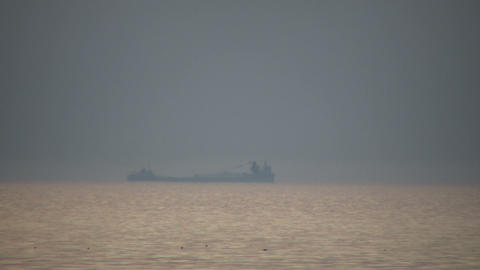 Transport ship passes by in the hazy distance (High... Stock Video Footage