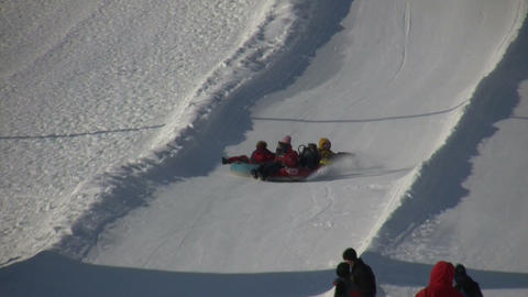 Winter scenic of people tubing down a hill (High Definition) Stock Video Footage