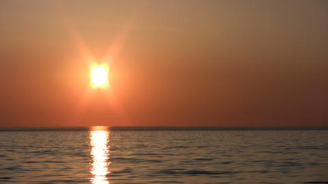 Sun hangs low and reflects in the water (High Definition) Stock Video Footage