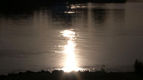 Setting sun is reflecting on the water's surface Footage