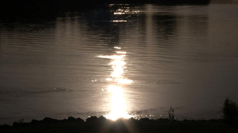 Setting sun is reflecting on the water's surface Stock Video Footage