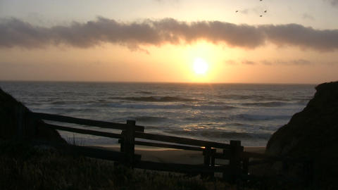 Sun is setting over the ocean in this beach scenic Footage