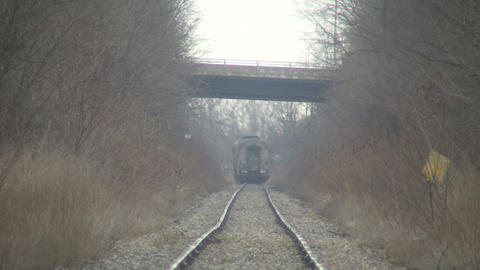 Train moves down tracks as cars pass overhead (High... Stock Video Footage