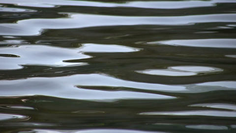 Closeup of water's surface rippling and reflecting sky (High Definition) Footage