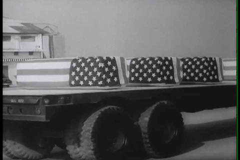 Flag draped coffins return from Vietnam during the Live Action