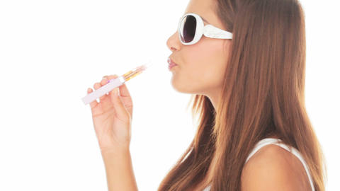 Beautiful woman smoking an e-cigarette Live Action