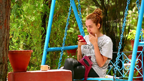 Female tourist on swing using her mobile phone Footage