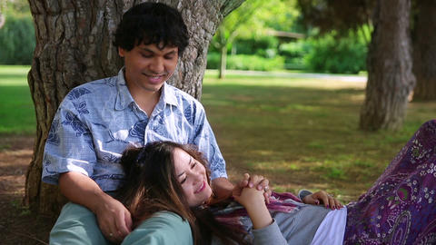 Young couple leaning against tree Footage