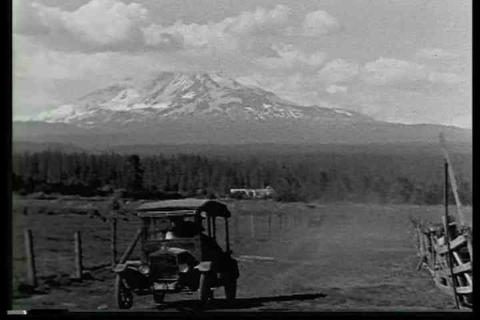 An old model T drives in front of a mountain range Footage