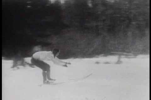 An old fashioned car pulls a skier behind in a spo Footage