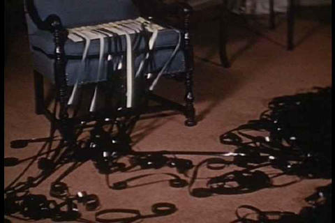 A filmmaker sits amongst reels and reels of 16mm f Footage