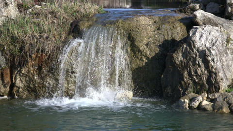 Closeup of a small waterfall splashing into pond (High... Stock Video Footage