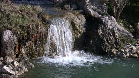 Closeup of a small waterfall splashing into pond (High Definition) Footage
