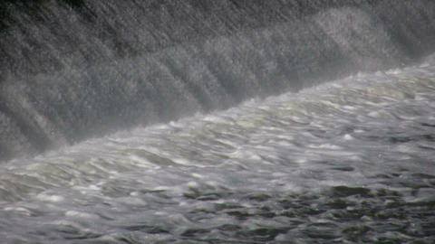 Water flows over a weir, creating small waterfall (High... Stock Video Footage