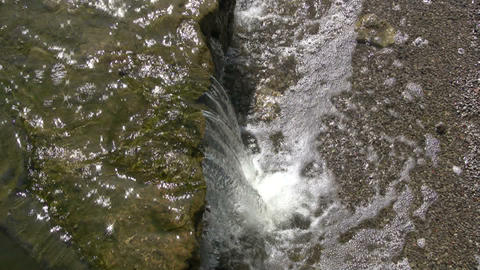 Topdown view of small waterfall splashing into pond (High Definition) Footage