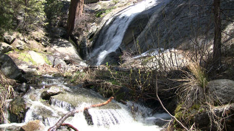 Small waterfalls flows down the rocks into a creek Stock Video Footage