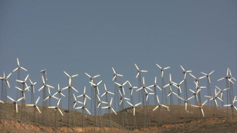 Wind turbines spin in the wind on a sunny day Stock Video Footage