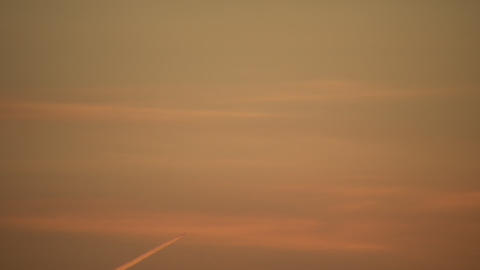 Condensation trails left behind from airplane at sunset... Stock Video Footage