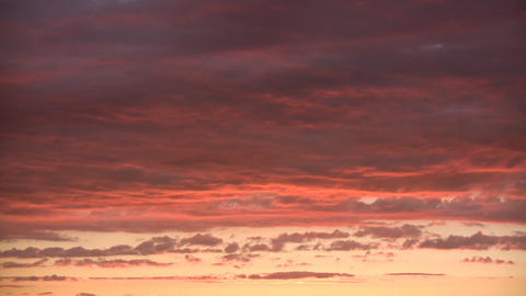 Timelapsed clouds are illuminated orange after the sunset (High Definition) Live Action