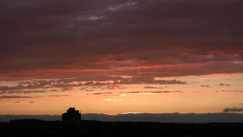 Timelapsed clouds are illuminated orange after the sunset... Stock Video Footage
