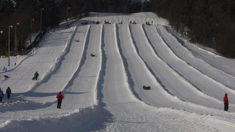 Winter scenic of people tubing down hill (High Definition, Timelapse) Footage