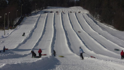 Winter scenic of people tubing down hill (High... Stock Video Footage