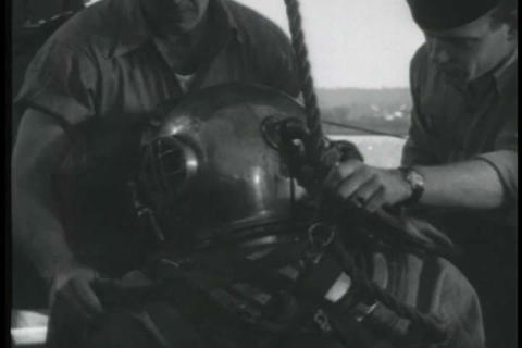 two men dress another man in deep sea diving gear  Live Action