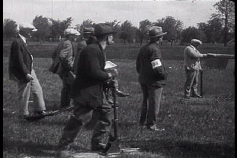 A group of men compete in a shooting contest durin Footage
