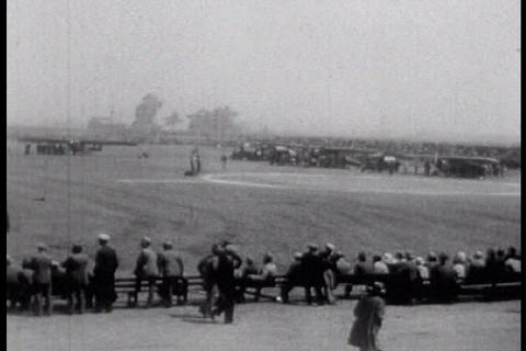 A crowd of people watch airplanes at an air-show d Footage