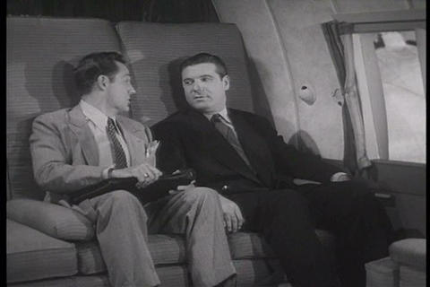 Two passengers on an airplane talk about cartoon a Footage