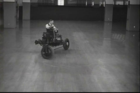 Indoor demonstration of a three wheeled tractor Live Action